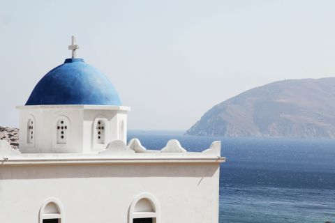 White church with blue coloured dome overlooking the Aegean