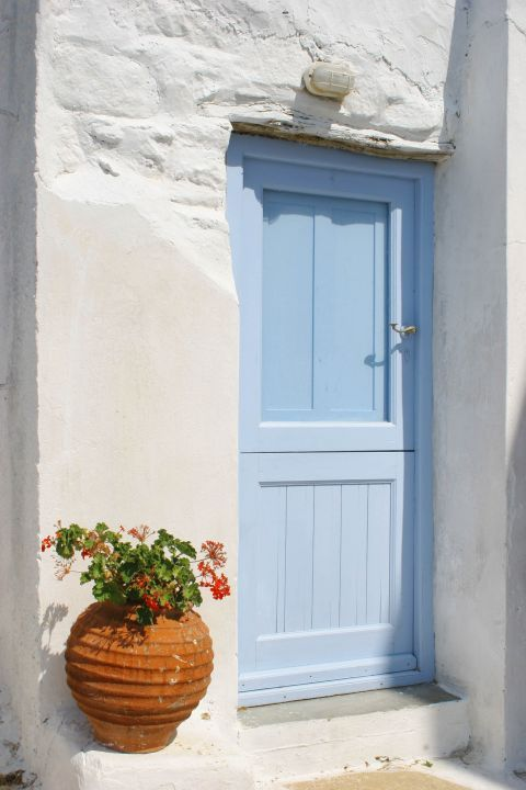 A ceramic vase with lovely flowers perfectly decorates the entrance of a traditional house.
