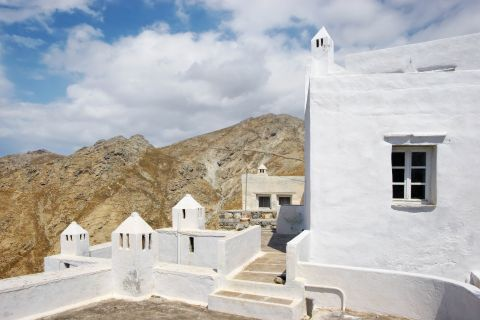 Whitewashed construction with some barren hills on the background.