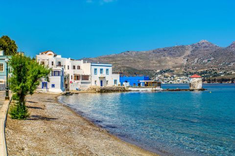 Whitewashed houses and a traditional windmill on Agia Marina beach