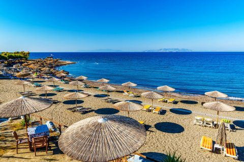 Umbrellas and sun loungers on the sandy beach of Kamiros.