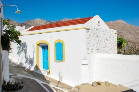 A whitewashed house with blue colored details. Megalo Chorio village, Tilos.