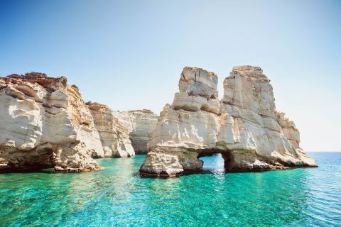 Turquoise waters and whitewashed rock formations, Milos.
