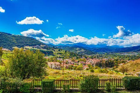 Green hills and mountains, lush vegetation and traditional houses in Kalavryta