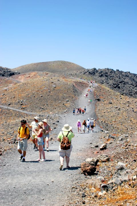 Tourists exploring the volcanic land of Santorini