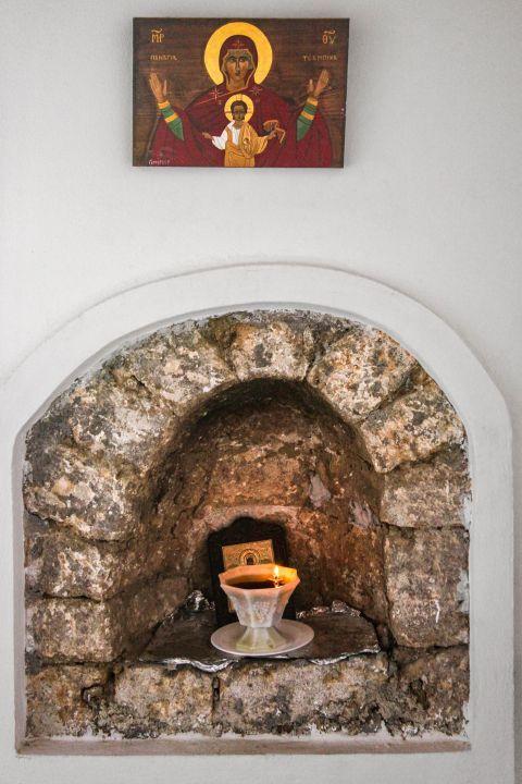 Panagia Tsambika: An icon of Panagia Tsambika and a candle.