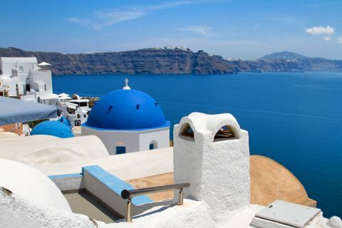 Whitewashed Cycladic buildings and the blue dome of a church