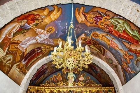 Agios Ioannis Monastery: A golden chandelier and religious paintings.