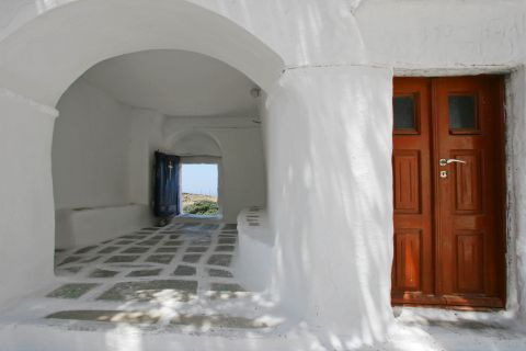 The Monastery of Taxiarches is painted in white color with a wooden door
