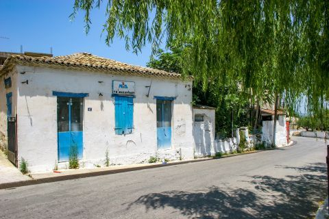 Maherado: An old building with ceramic roof tiles. It is whitewashed with blue colored details.