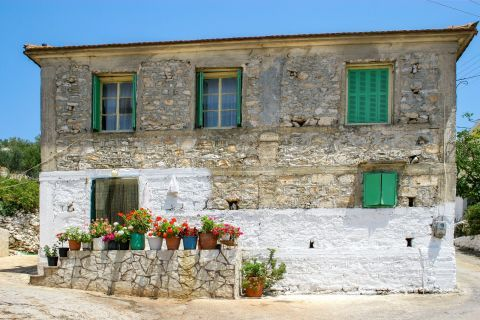 Exo Hora: A stone built, two-floored house with lovely flower pots.
