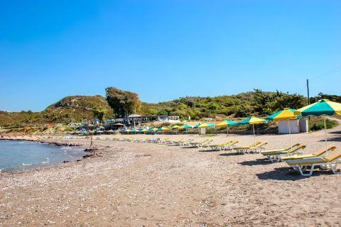 Kamiros: Umbrellas and sun loungers on the waterfront of Kamiros beach.