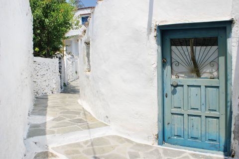 Driopida: A white-colored house with a blue, wooden door.