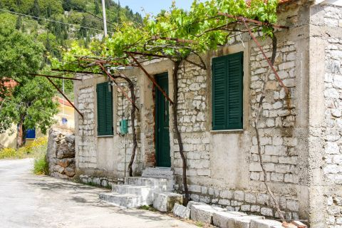 Exogi: A stone built house with colorful shutters.