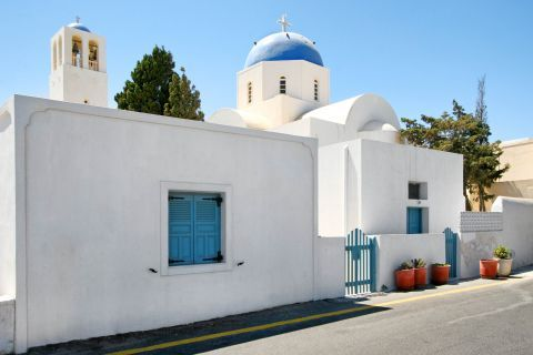 Firostefani: A whitewashed church with a blue-colored dome