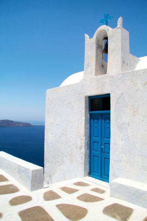 Firostefani: A whitewashed chapel with a blue-colored door