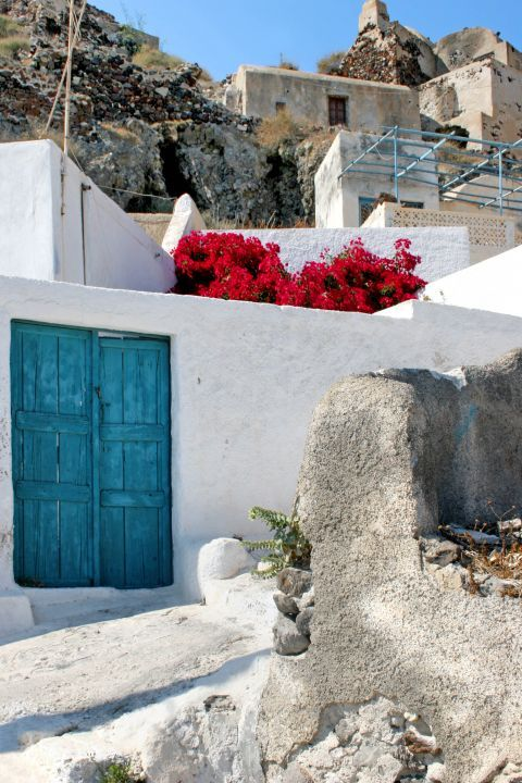 A whitewashed house with beautiful flowers and a blue door