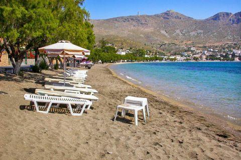 Alinda beach: Some umbrellas and sun loungers.