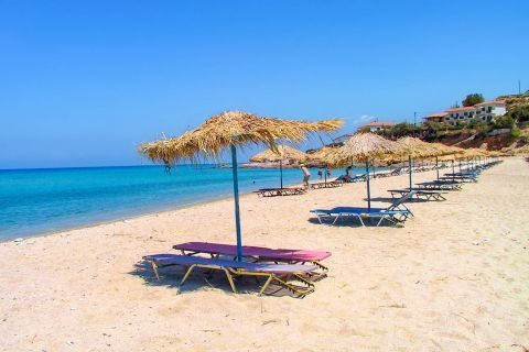 Livadi: Some umbrellas and sun loungers by the sea.