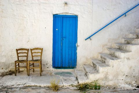 Megalochori: A whitewashed house with a blue, wooden door.
