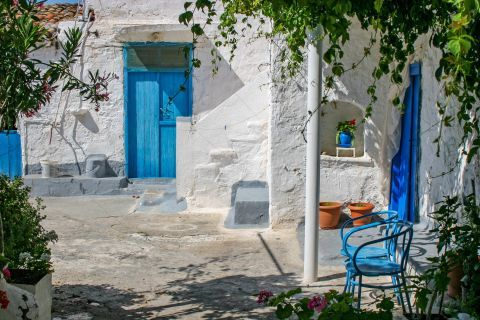 Megalochori: A house with a lovely yard, painted in white and blue colors.