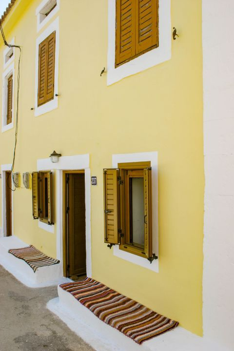 Agios Leon: A well preserved two floored building with wooden shutters, painted in light yellow color.
