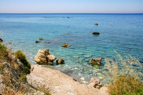 Apidies: This rocky coast has clean water and it is surrounded by much greenery.