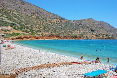 Plaka: Pebbled beach with clear, azure waters.