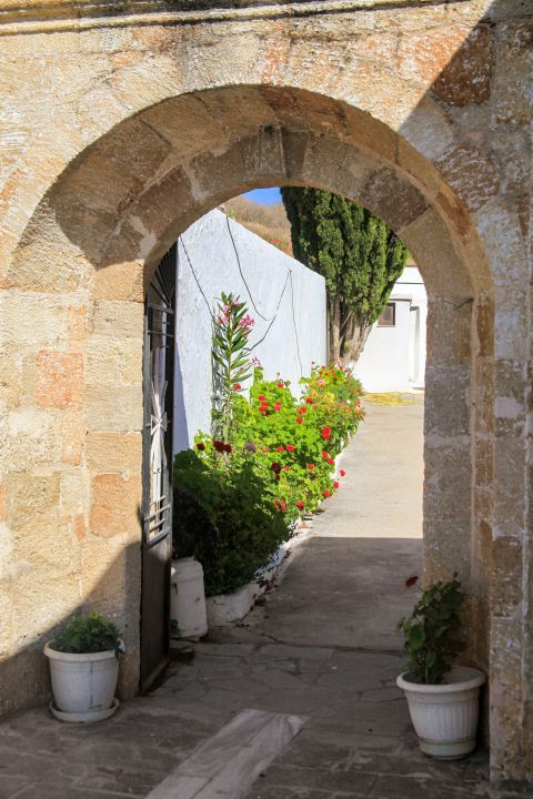 Apolakia: A stone built arch with some flower pots.