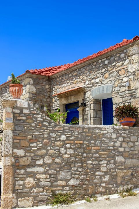 Genadi: A stone built house with blue colored shuters and flower pots.