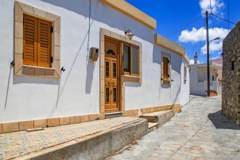 Mesanagros: A well mainteined house, painted in white, with wooden door and shutters.