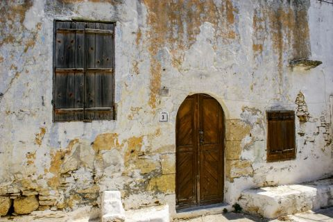 Paradisi Village: An old house with wooden doors and shutters.