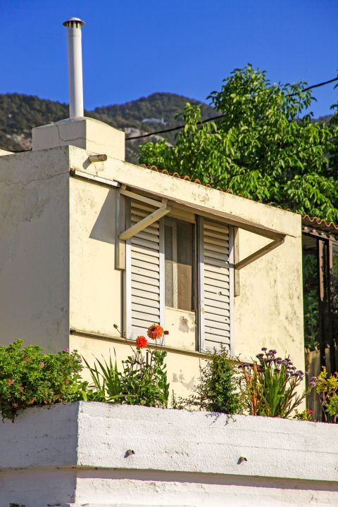 Salakos: The window of an old house, painted in pale colors.