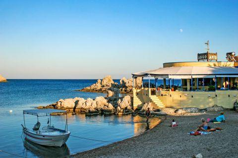Haraki: A tavern and a fishing boat. A tranquil spot on Haraki beach.
