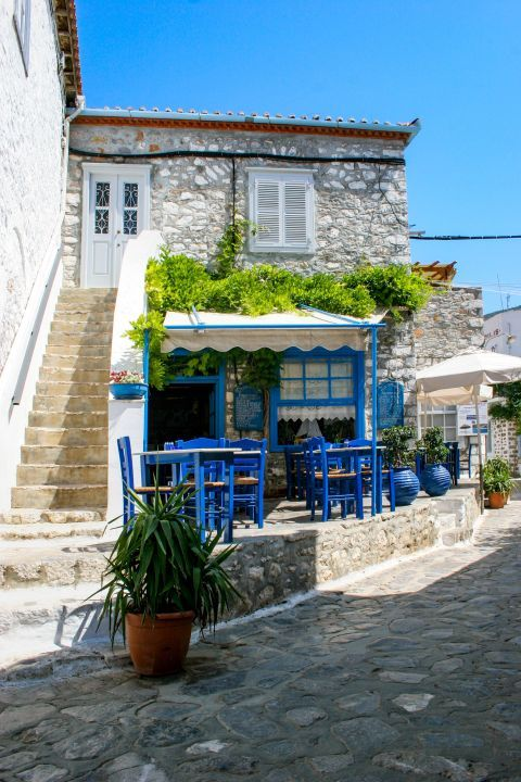 Town: A vintage, stone-built house and a tavern with blue-colored decoration.