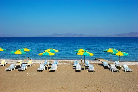 Ialissos: Sun loungers and umbrellas by the sea.