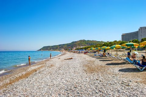 Ialissos: The coastline of Ialyssos beach is covered with sand and pebbles.