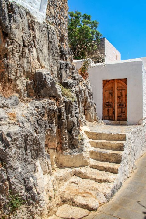 Lindos: A traditional, small house, built next to an abrupt cliff.