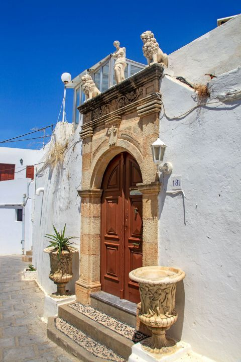 Lindos: The entrance of an old house, decorated with exquisite, small, marble statues