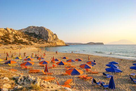Arkassa: Sandy beach with umbrellas and sun loungers.
