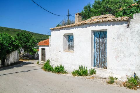 Anafonitria: A whitewashed house with old, wooden shutters and windows.