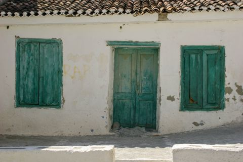 Whitewashed house with green-colored shutters and door.