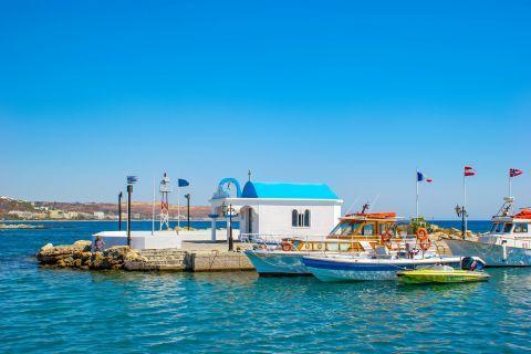 Faliraki: A small chapel in white and blue colors and some sailing boats close to the harbor of Faliraki.