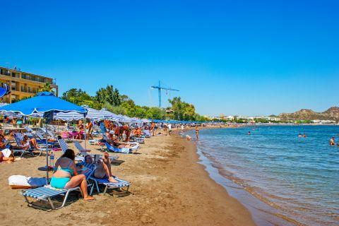 Faliraki: Umbrellas and sun loungers on the waterfront of Faliraki beach.