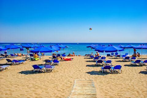 Faliraki: Blue colored umbrellas and sun loungers on Faliraki beach.