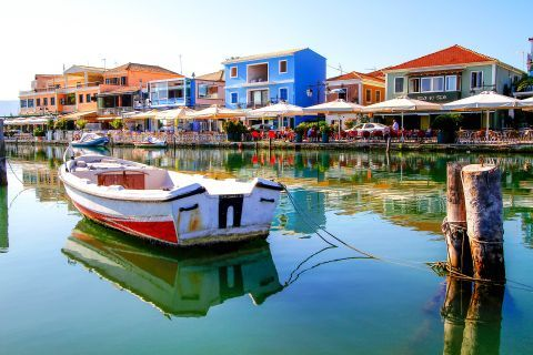 A small boat, mooring on the turquoise waters of the port of Lefkada Town.