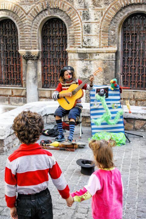 Syntagma: A street musician entertaining small kids