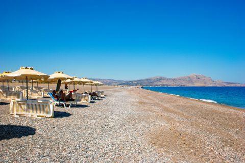 Kalathos: Umbrellas and sun loungers by the sea.