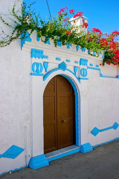 Koskinou: Whitewashed house with beautiful decoration and a wooden door.