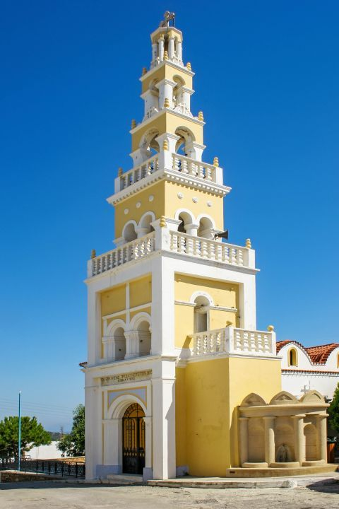Koskinou: Tall, impressive belfry, painted in light yellow and white colors.
